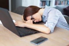 Утомленная женщина брюнет спать перед компьтер-книжкой внутри помещения Стоковая Фотография