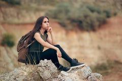 Утомленная женщина сидя на скалистой скале стоковое фото