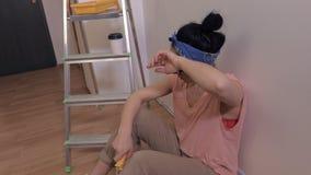 Утомленная женщина с щеткой ролика краски около стены видеоматериал