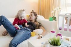 Утомленная мама спать пока сидящ с детьми стоковое изображение