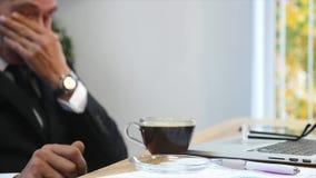 Утомленная отделка бизнесмена работая в офисе и выпивая кофе Селективный фокус акции видеоматериалы