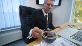 Утомленная отделка бизнесмена работая в офисе и выпивая кофе Селективный фокус движение медленное видеоматериал