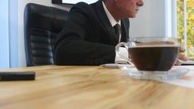 Утомленная отделка бизнесмена работая в офисе и выпивая кофе Селективный фокус движение медленное сток-видео