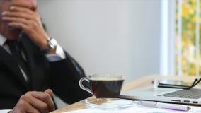 Утомленная отделка бизнесмена работая в офисе и выпивая кофе Селективный фокус Стоковые Изображения