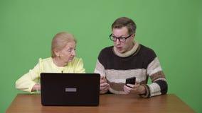 Утомленная старшая коммерсантка используя компьтер-книжку и молодой человек осадки используя телефон видеоматериал