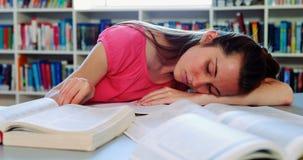 Утомленная школьница спать в библиотеке пока делающ домашнюю работу акции видеоматериалы