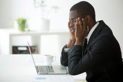 Утомленное Афро-американское страдание от головной боли и массажировать tem стоковая фотография