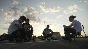 Утомленные пробуренные друзья при велосипеды стоя вниз на улице используя smartphones с заходом солнца и птицами в предпосылке - сток-видео