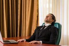 Утомленный бизнесмен отдыхая на таблице Стоковое Фото