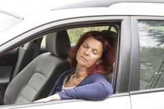 Утомленный водитель женщины спит в автомобиле Стоковое Изображение
