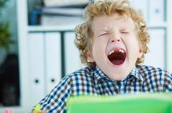 Утомленный зевок школьника сидя на таблице в классе на уроке Стоковая Фотография RF