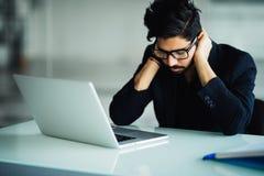 Утомленный и потревоженный индийский бизнесмен на рабочем месте в офисе держа его голову на руках стоковые изображения rf