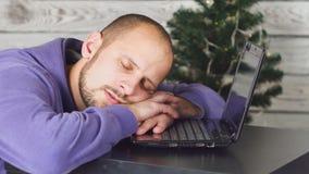 Утомленный молодой бизнесмен в офисе на кануне Нового Годаа Рождественская елка в офисе компьтер-книжка стола владение домашнего  акции видеоматериалы