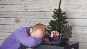 Утомленный молодой бизнесмен в офисе на кануне Нового Годаа Рождественская елка в офисе компьтер-книжка стола владение домашнего  сток-видео