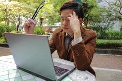 Утомленный молодой бизнесмен держа стекла и страдая Не напряжен зрения перед компьтер-книжкой экрана на внешнем парке стоковое изображение
