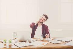 Утомленный, перегружающ бизнесмена с компьтер-книжкой в современном белом офисе Стоковая Фотография