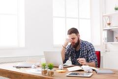 Утомленный, перегружающ бизнесмена с компьтер-книжкой в современном белом офисе Стоковая Фотография RF