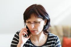 Утомленный средн-постаретый звонок женщины телефоном Стоковое Изображение