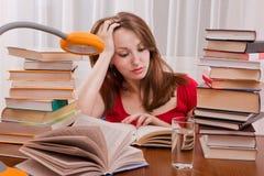 Утомленный студент имея много прочитать. Стоковые Изображения RF