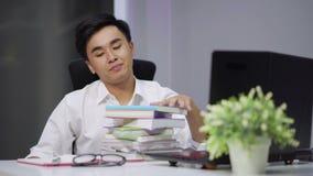 Утомленный студент сидя на таблице с книгой и компьтер-книжкой акции видеоматериалы