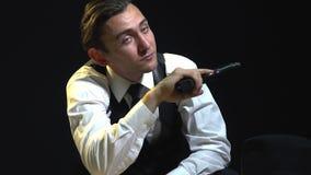Утомленный человек в костюме сидит на таблице с пистолетами к его руке и выправляет его волосы сток-видео