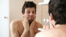 Утомленный человек который как раз просыпал вверх по смотреть его отражение в зеркале и трет его щеки с обеими руками видеоматериал
