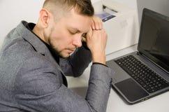 Утомленный человек с закрытой склонностью глаза и головных против рук Стоковые Фотографии RF