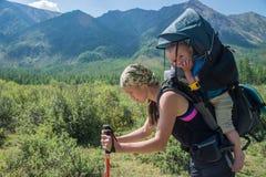 Утомленный Hiker женщины trekking в горах с ребенком в рюкзаке, остановленном для матери остатков при ребёнок путешествуя внутри Стоковое фото RF