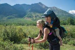 Утомленный Hiker женщины trekking в горах с ребенком в рюкзаке, остановленном для матери остатков при ребёнок путешествуя внутри Стоковые Изображения