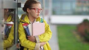 Утомлянная девушка в красных стеклах и желтой куртке вздыхает положение около школы Нагрузка исследования, затруднения в школе сток-видео