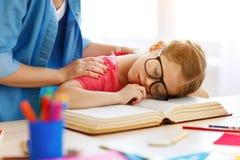 Утомлянная девушка ребенка упала уснувший когда она сделала ее домашнюю работу дома стоковые фотографии rf
