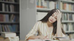 Утомлянная женщина брюнета подготавливает для рассмотрения на университетской библиотеке сток-видео
