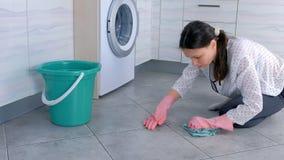 Утомлянная женщина в розовых резиновых перчатках моет и трет крепко пятно на поле кухни с тканью Серые плитки на поле сток-видео