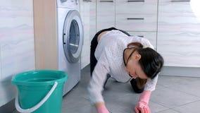 Утомлянная женщина в розовых резиновых перчатках моет и трет пол кухни с тканью Серые плитки на поле видеоматериал