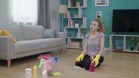 Утомлянная женщина обтирает ее лоб после очищать ее квартиру сток-видео