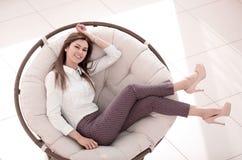 Утомлянная молодая женщина ослабляет в мягком круглом стуле стоковые изображения rf