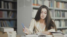 Утомлянная молодая женщина подготавливает для рассмотрения на университетской библиотеке акции видеоматериалы