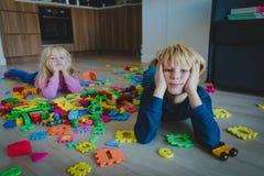 Утомлянные мальчик и девушка усилили вымотанный с игрушками разбросанными внутри помещения стоковые изображения