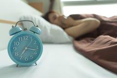 Утомлянный будить зевка молодой женщины держащ будильник бодрствование вверх по ea стоковое изображение