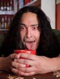 утомлянный красный цвет человека latino чашки кофе cradling Стоковые Изображения