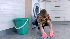 Утомлянный мальчик в резиновых перчатках не хочет мыть пол в кухне Обязанности ребенка домашние сток-видео