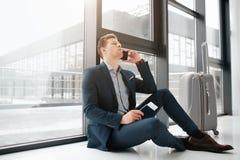 Утомлянный молодой бизнесмен сидит на окне и беседе на телефоне Он ждет Билет владением Гай в паспорте Его чемодан стоит стоковое изображение rf