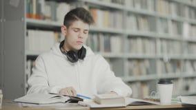 Утомлянный студент подготавливает для рассмотрения на университетской библиотеке видеоматериал
