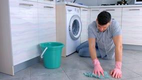 Утомлянный человек в резиновых перчатках моет и трет пол в кухне, сидя на поле акции видеоматериалы