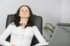 Утомленная бизнес-леди упала уснувший рядом с компьтер-книжкой Стоковые Изображения