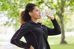 Утомленная здоровая питьевая вода женщины в парке Стоковое Изображение RF