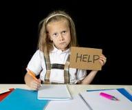 Утомленная милая младшая школьница при светлые волосы сидя в стрессе работая делающ домашнюю работу смотря пробуренный Стоковые Изображения