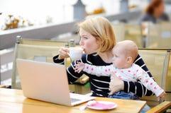 Утомленная молодая мать держа дочь 6 месяцев и выпивая кофе стоковые фотографии rf