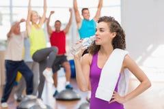 Утомленная питьевая вода женщины на фитнес-клубе Стоковые Изображения