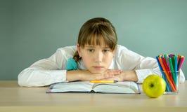 Утомленная школьница отдыхая на книге на столе Стоковые Фотографии RF